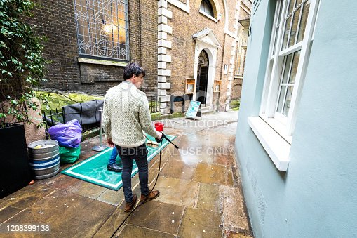 London, UK - 17 February, 2020: wide angle color image depicting a caucasian male cleaning a narrow London city street using a pressure hose. The man is surrounded by traditional architecture on either side of the narrow path.