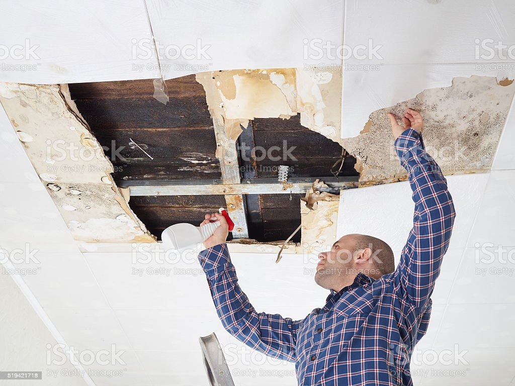 Mann Reinigung und Schimmel an der Decke. – Foto