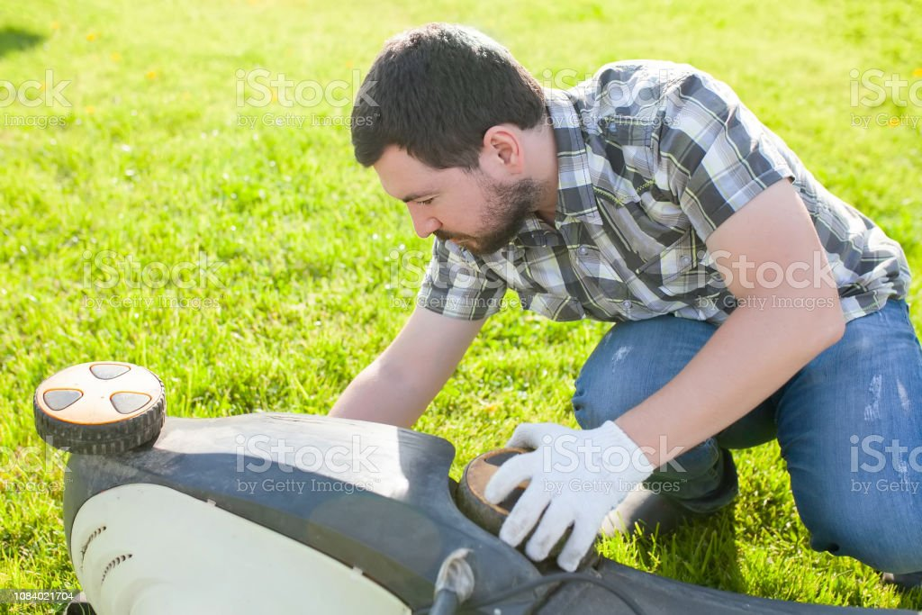 Man cleaning or fixing lawn mower blade. stock photo