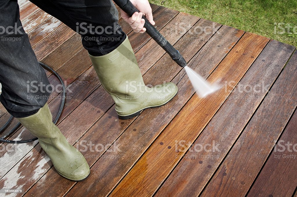 Man Cleaning Patio Decking With a Pressure Hose stock photo