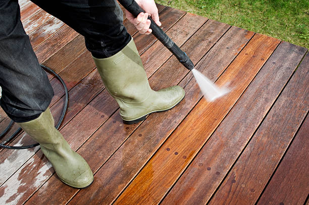 man cleaning patio decking with a pressure hose - high pressure cleaning stock photos and pictures