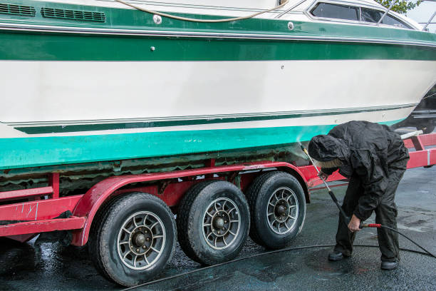 man cleaning power boat with pressure washer stock photo