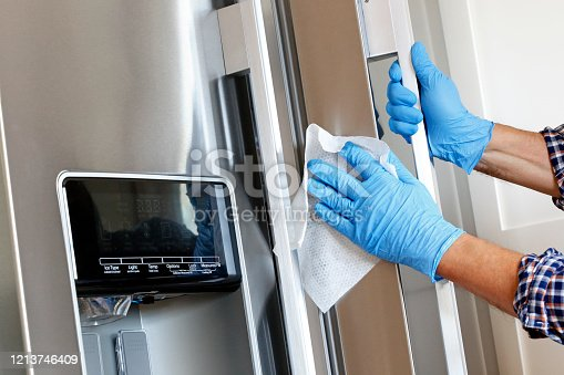 A close up of a Hispanic man wearing disposable gloves as he cleans a stainless steel refrigerator door handle with a disinfectant wipe.