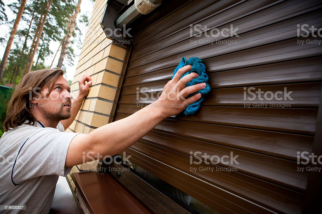 man cleaning roller shutters stock photo