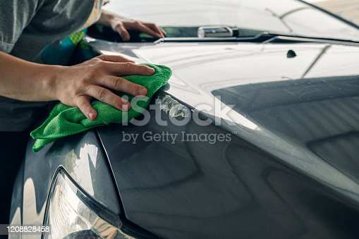 Man cleaning scratch on car with green microfiber cloth and cleaner remover