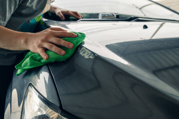 Man cleaning scratch on car with microfiber cloth and cleaner remover stock photo