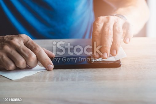 Man cleaning smartphone screen with cloth before applying protective cover foil