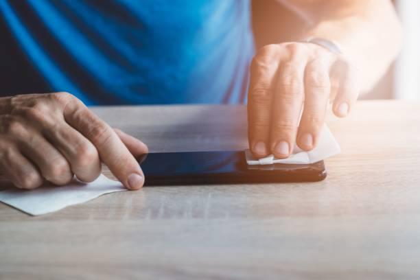 Mann, die smartphonebildschirm mit Tuch reinigen – Foto