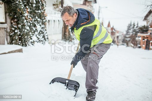 One man, prepared for clean the street full on snow, working with snow shovel.