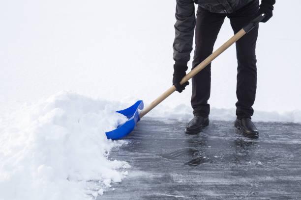 男子用藍鏟從冰面上為滑冰清理積雪。冬季常規概念。 - 鏟 個照片及圖片檔