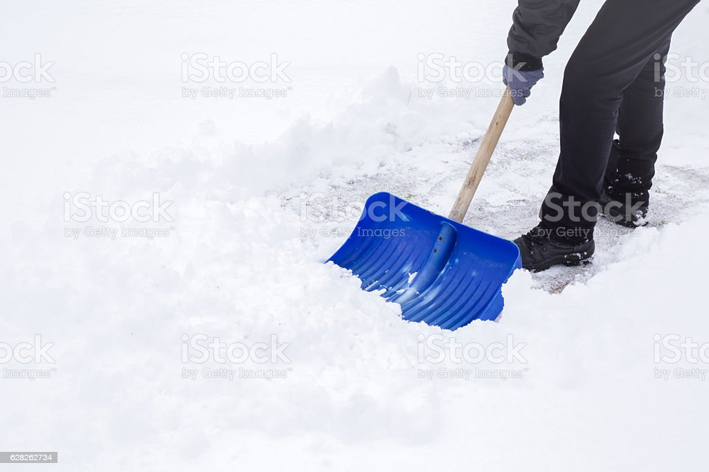 Man cleaning snow with shovel in winter day. stock photo