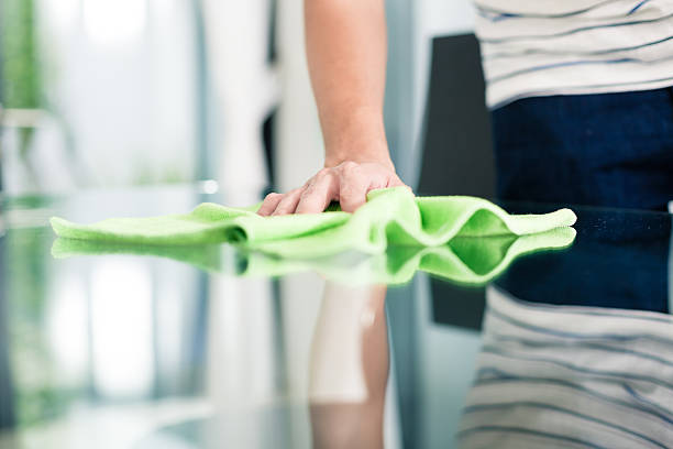 Man cleaning table in home with cloth stock photo
