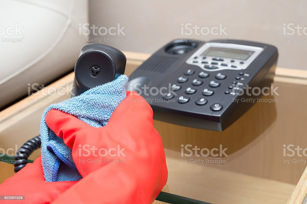 man cleaning telephone with a blue cloth stock photo