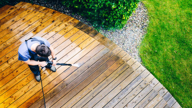 man cleaning terrace with a power washer - high water pressure cleaner on wooden terrace surface stock photo