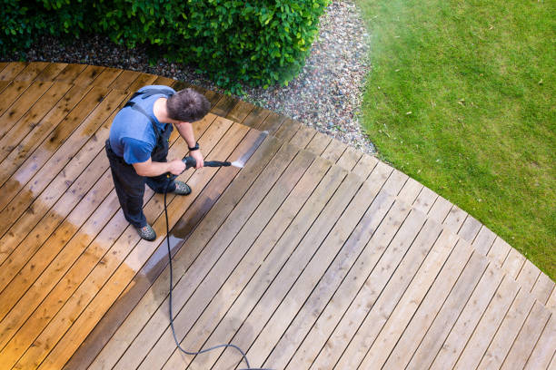 man cleaning terrace with a power washer - high water pressure cleaner on wooden terrace surface - forza foto e immagini stock