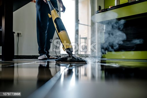Man cleaning the floor with a dry steam cleaner