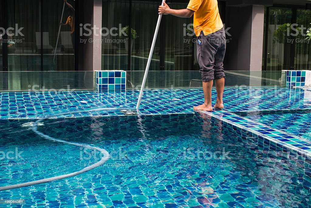 Man cleaning the swimming pool with vacuum cleaner stock photo