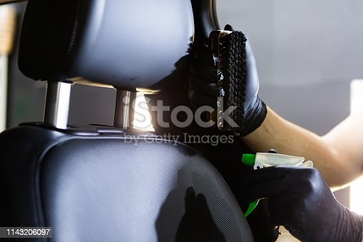 Dry cleaner's employee hand cleaning a car's gray textile seats with professionally blue brush. Early spring regular cleanup. Care about auto interior. Commercial cleaning company concept
