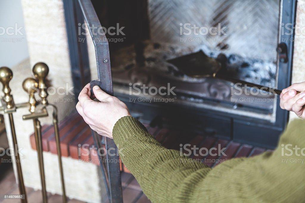 Man cleans brass fireplace shovel stock photo