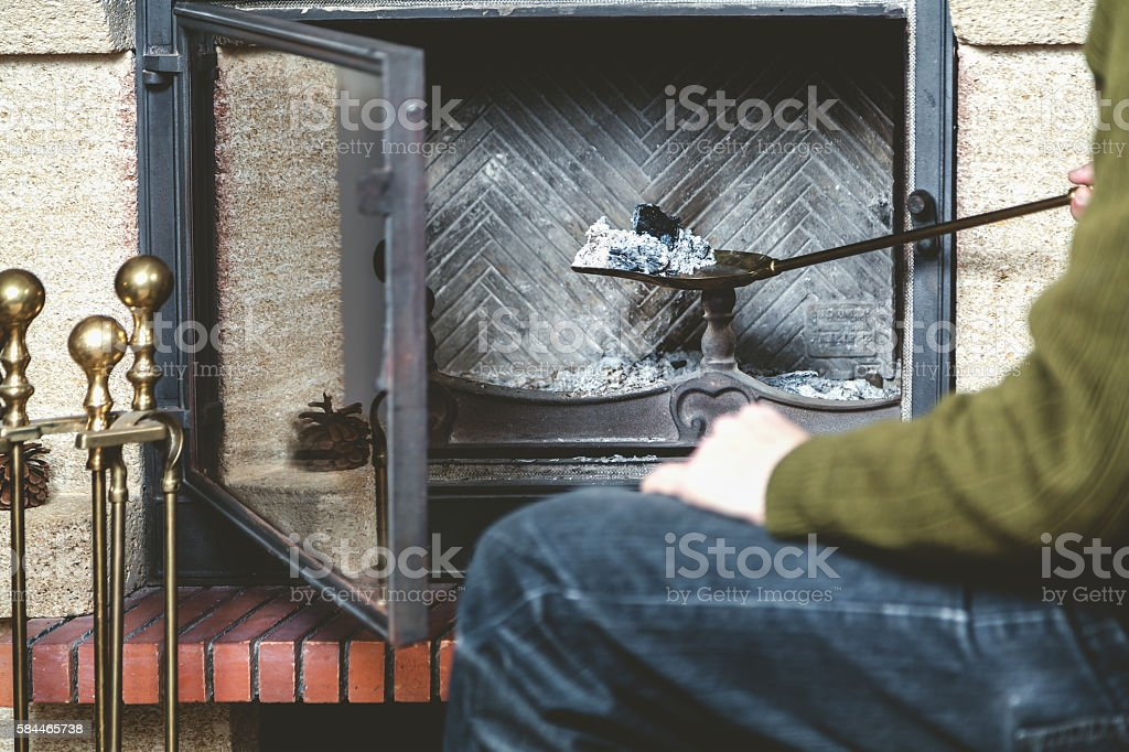man cleans fireplace with spatula stock photo