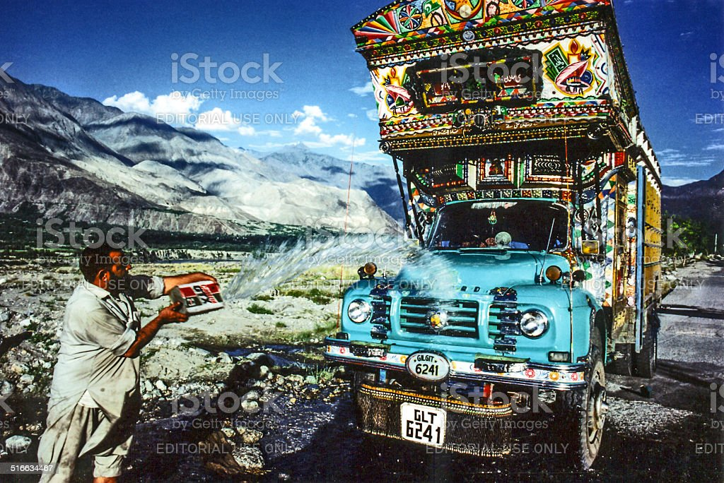 man cleans his overland truck with water from a creek stock photo