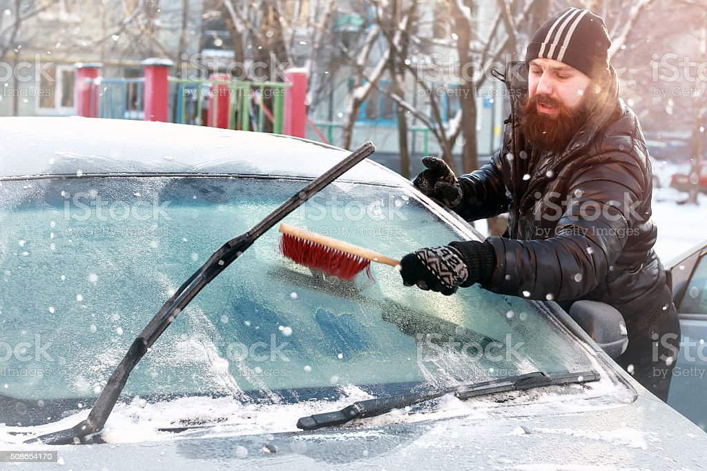 man cleans snow from the glass at the car stock photo