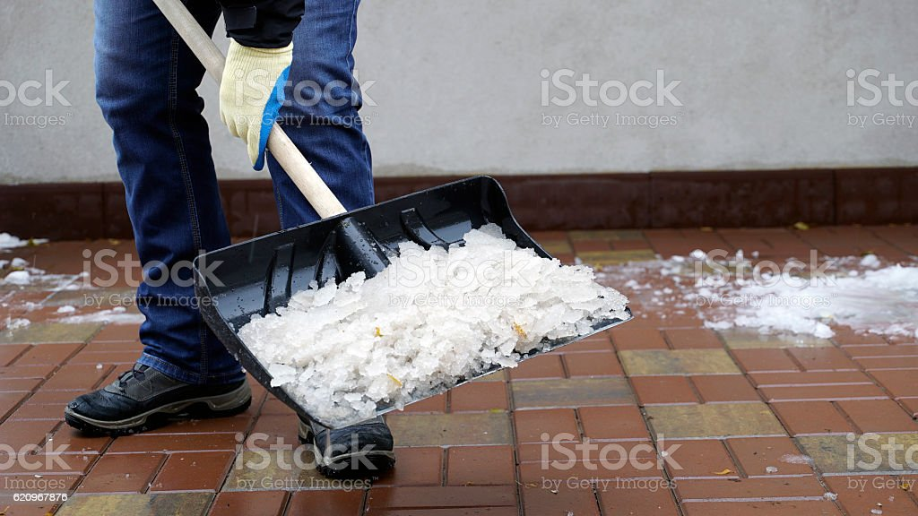 man cleans snow from the yard stock photo