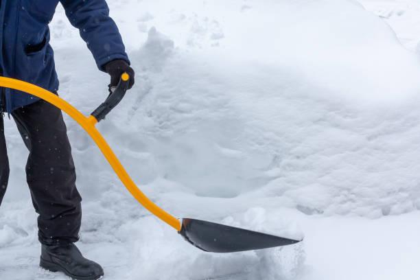 Ein Mann reinigt Schnee im Hof mit einer Schaufel nach einem starken Schneefall – Foto