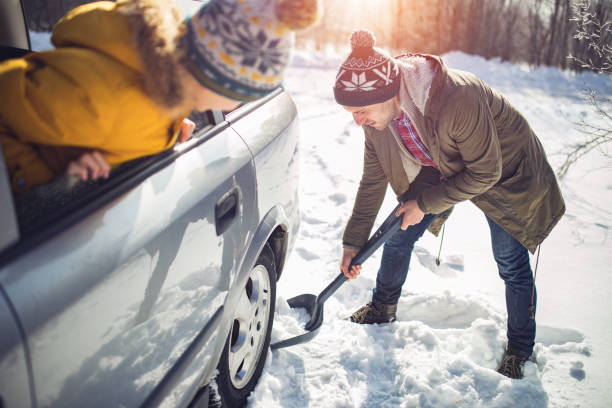 Man cleans snow near the car  in nature stock photo