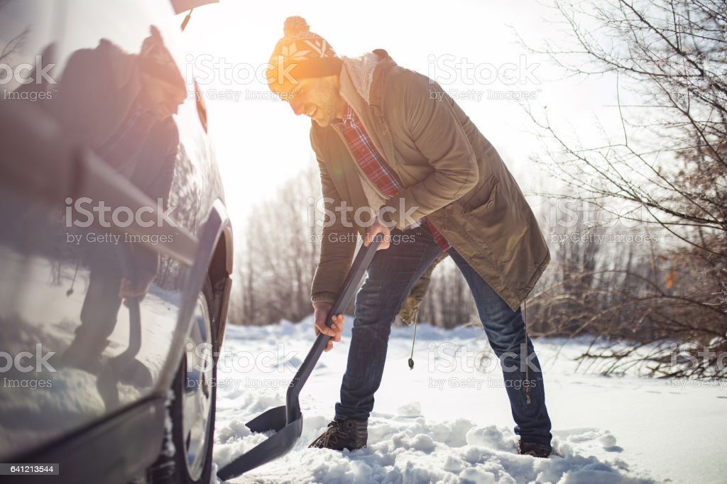 Man cleans snow near the car with shovel in nature stock photo