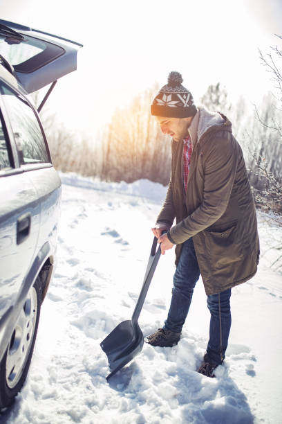 Man cleans snow near the car with shovel stock photo
