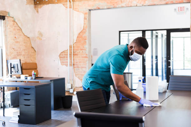 Man cleans table in office during COVID-19 stock photo