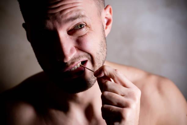 hombre limpia el espacio entre los dientes con un palillo de dientes - foto de stock