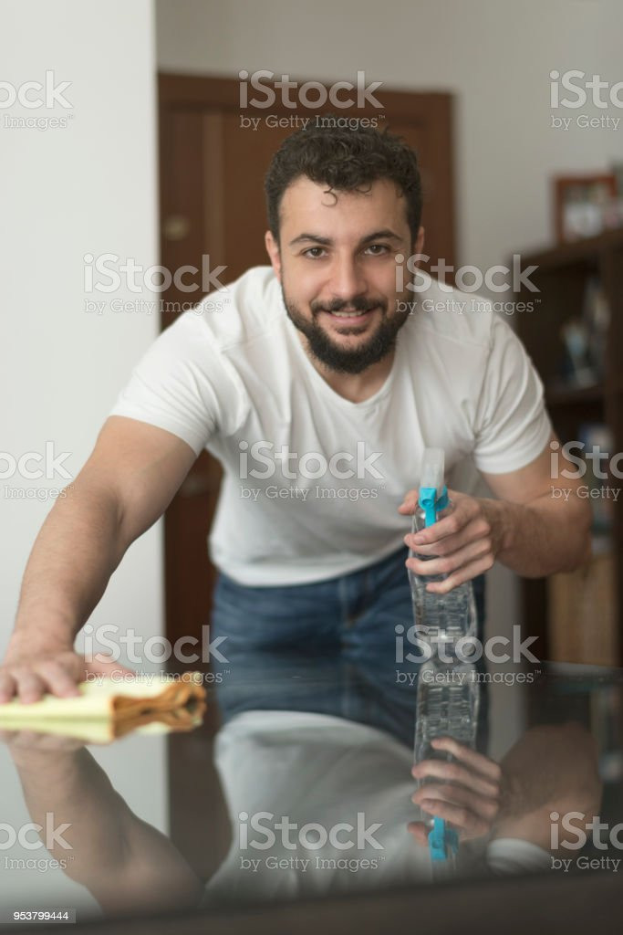 man cleans the windows of the house with multipurpose glass cleaner pulverizer. stock photo