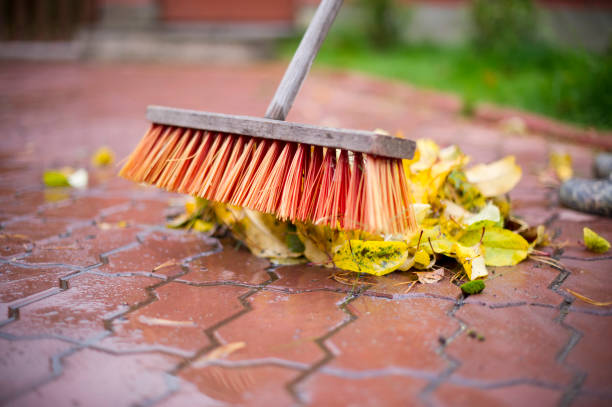 hombre limpia con una escoba hojas de otoño de cerca - foto de stock