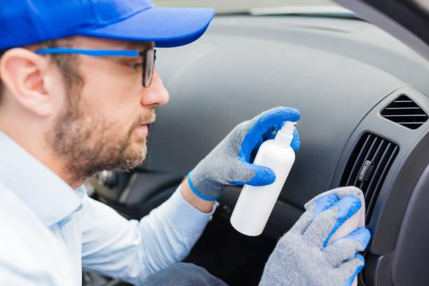 Hombre que limpia el conducto de aire de la rejilla de ventilación del coche y la pulverización con líquido de desinfección. - foto de stock
