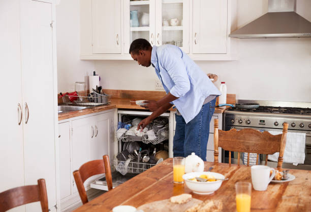 Man Clearing Breakfast Table And Loading Dishwasher Man Clearing Breakfast Table And Loading Dishwasher dishwasher stock pictures, royalty-free photos & images