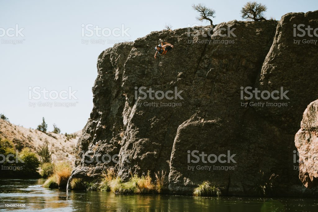 Man Cliff Jumping Into Deschutes River in Eastern Oregon stock photo