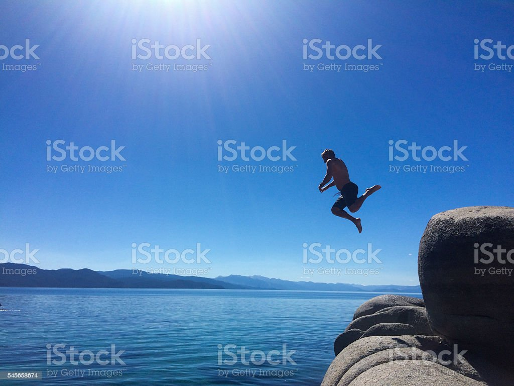 Man cliff jumping into Lake Tahoe stock photo