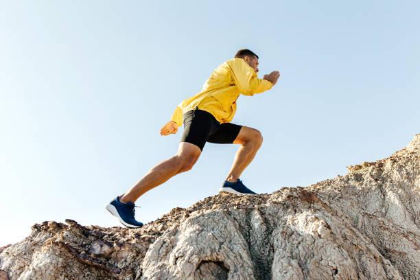 hombre escalar montaña cuesta arriba - foto de stock
