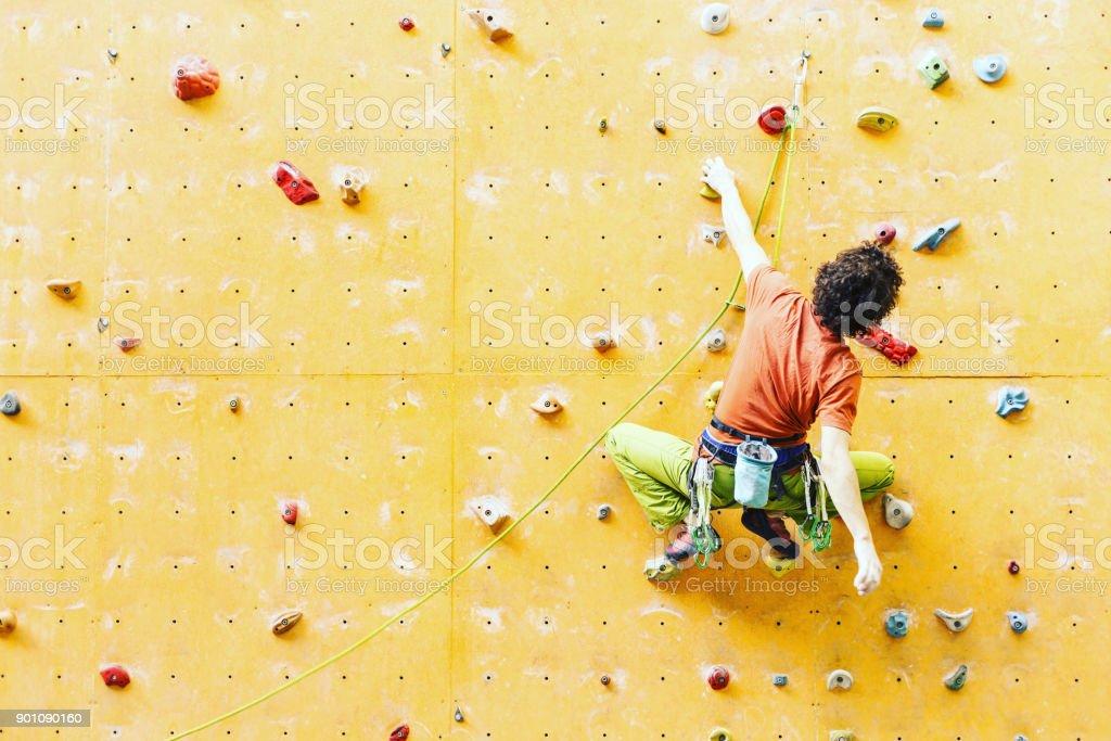 Mann Bergsteiger auf künstliche Kletterwand in Bouldern Turnhalle – Foto