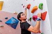 istock Man climber on artificial climbing wall 1158641084