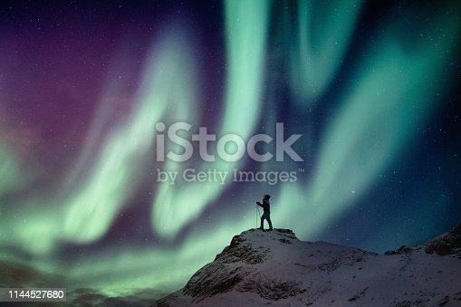 istock Man climber standing on snowy peak with aurora borealis and starry 1144527680