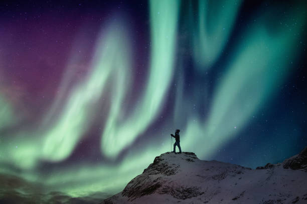 Man climber standing on snowy peak with aurora borealis and starry stock photo