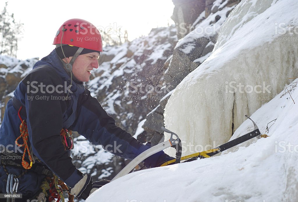 Man climbing a frozen waterfall royalty-free stock photo