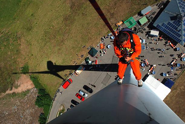 Man climbing down a wind turbine stock photo
