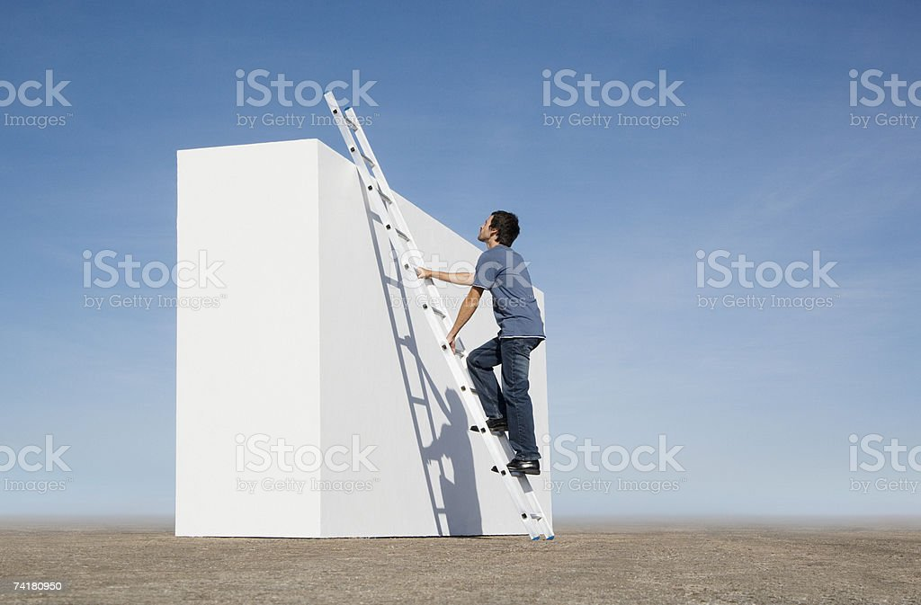 Man climbing ladder against wall outdoors royalty-free stock photo
