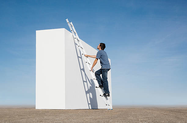 man climbing ladder against wall outdoors - ladder stock photos and pictures