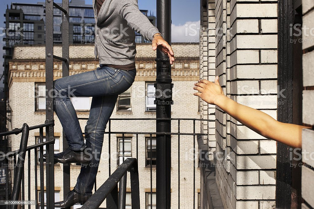 Man climbing ladder in balcony, stretching hand for woman royalty-free stock photo