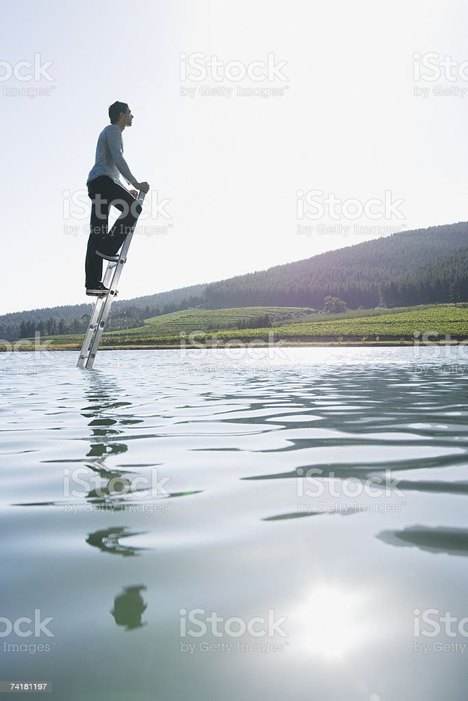 Man climbing ladder in water with trees royalty-free stock photo